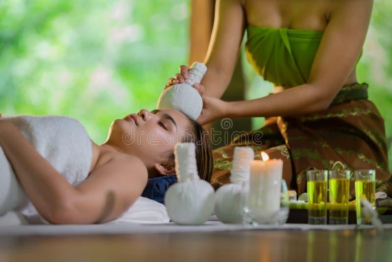 Mulher bonita nova de Ásia durante a massagem com a compressa erval dos termas com óleo e grupo erval perto do local, do relaxame imagem de stock