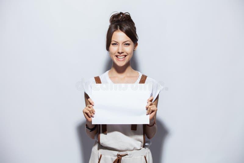 Mulher bonita nova de sorriso que mostra o quadro indicador vazio, sobre o fundo branco isolado foto de stock royalty free