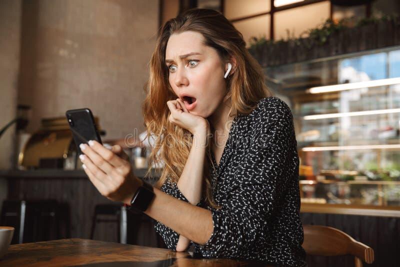 Mulher bonita nova bonita desagradada chocada assustado que senta-se no café que usa dentro o telefone celular que fala com amigo foto de stock