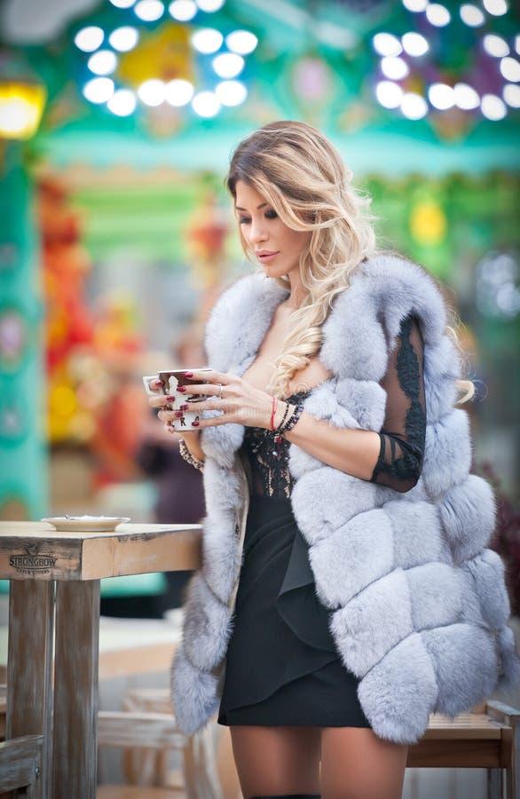 Mulher bonita nova do cabelo justo longo elegante com casaco de pele branco, tiro exterior em um dia de inverno frio Menina loura fotografia de stock royalty free