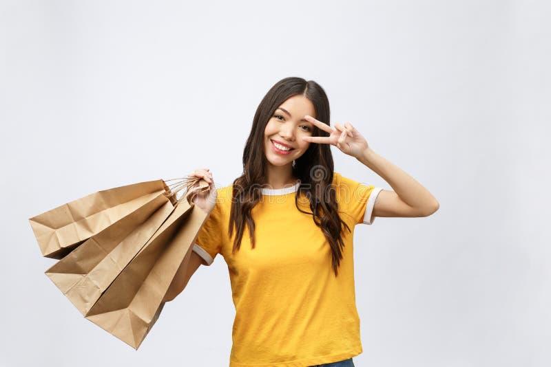 A mulher bonita nova do cliente com sacos de compras mostra dois dedos Fundo branco isolado foto de stock