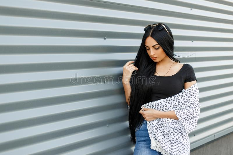 Mulher bonita nova do moderno com cabelo longo em óculos de sol redondos em uma parte superior na moda preta em um revestimento d imagens de stock royalty free