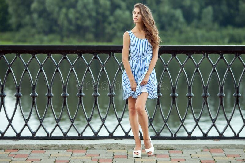 A mulher bonita nova do retrato completo do comprimento no azul branco listrou o vestido, parque do rver do verão fora imagens de stock