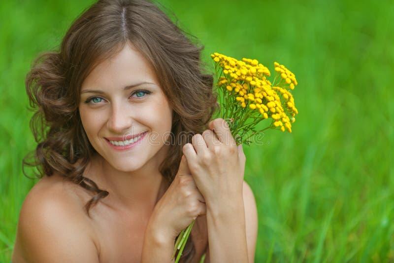 Mulher bonita nova do retrato que guardara o wildflower amarelo do ramalhete foto de stock royalty free