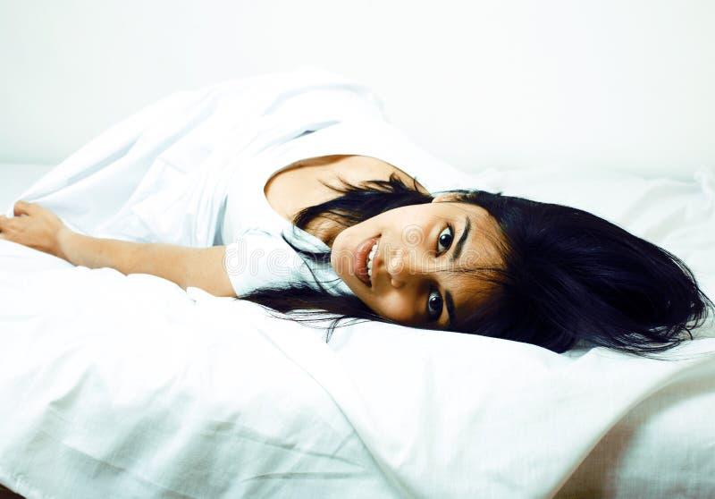 Mulher bonita nova do tann na cama entre as folhas brancas que têm o divertimento, tentando dormir, enganando ao redor fotografia de stock royalty free