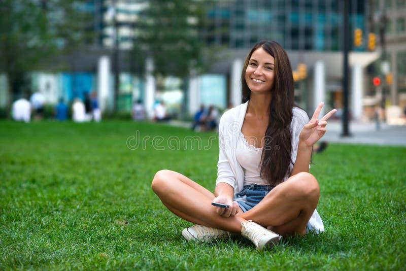 Mulher bonita nova do turista caucasiano que senta-se na grama verde no parque da cidade e que mostra o sinal da vitória v fotografia de stock