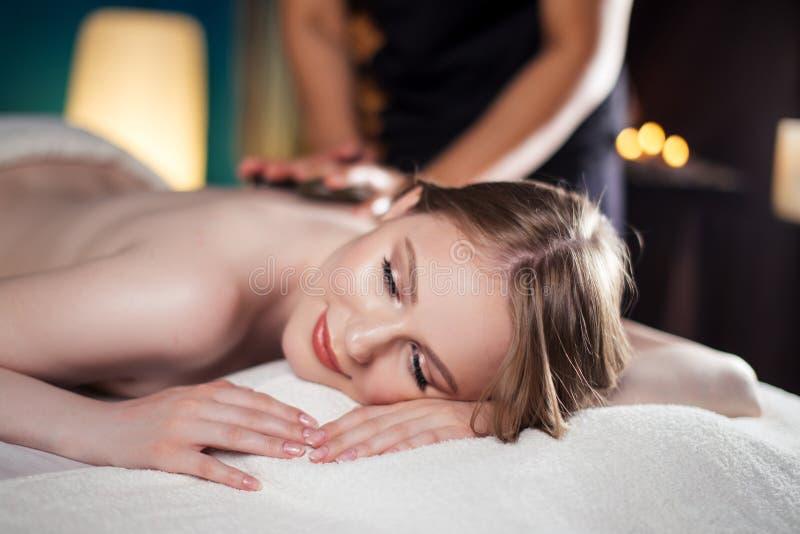 A mulher bonita, nova e saudável está tendo a massagem de pedra quente Termas - 7 imagens de stock