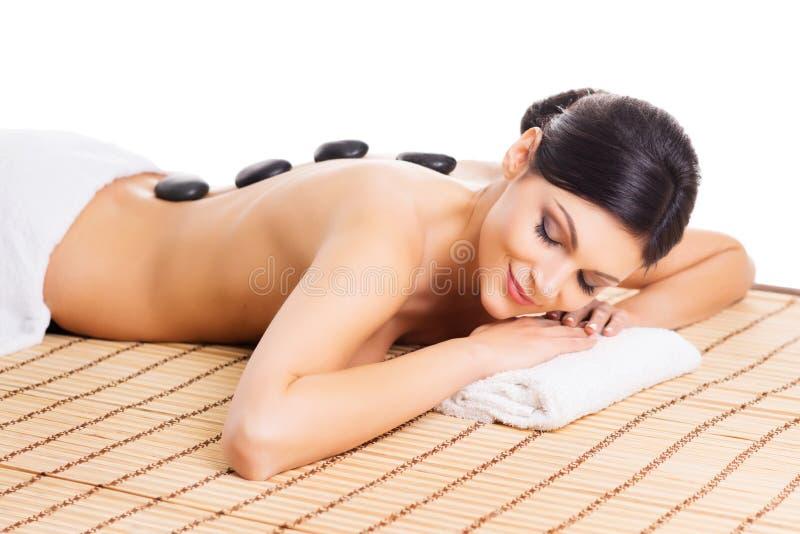A mulher bonita, nova e saudável na esteira de bambu no salão de beleza dos termas está tendo a massagem de pedra quente imagem de stock