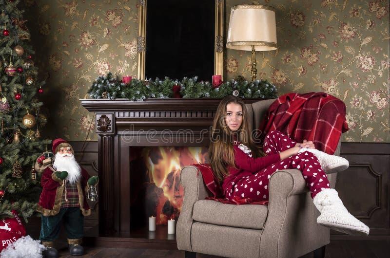 A mulher bonita nova em pijamas vermelhos da roupa da casa do Natal e nas botas brancas da casa senta-se em uma cadeira na perspe imagem de stock