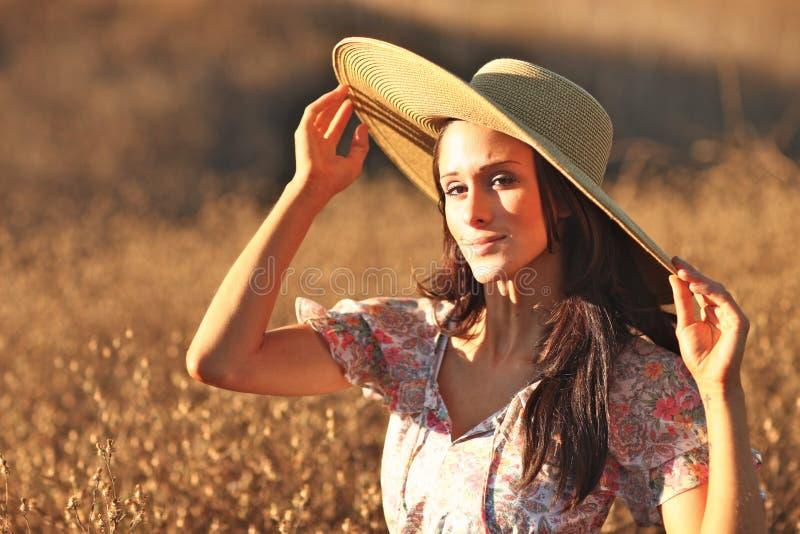 Mulher bonita nova em um campo no tempo de verão fotografia de stock