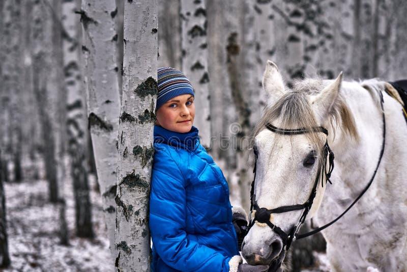 Mulher bonita nova em um casaco azul e em um chapéu dos esportes para uma caminhada com um cavalo branco na floresta do vidoeiro  fotos de stock