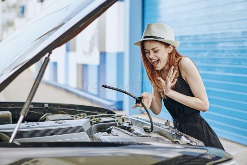 A mulher bonita nova em um chapéu do branco repara um carro na rua fotos de stock