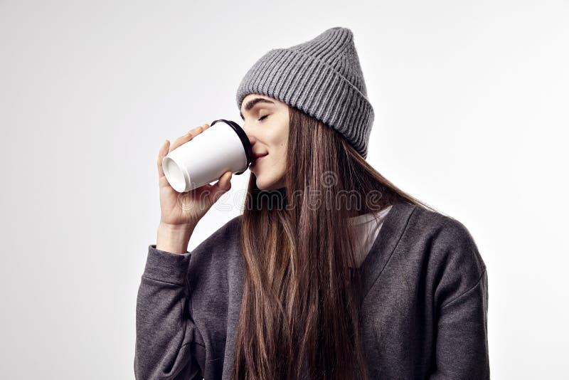 Mulher bonita nova em um equipamento cinzento que bebe um café do copo de papel Disposição de projeto afastada do pacote fotos de stock royalty free
