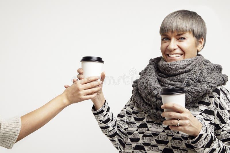 Mulher bonita nova em um equipamento cinzento que come um café do copo de papel Disposição de projeto afastada do pacote imagem de stock royalty free