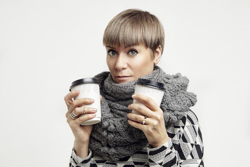 Mulher bonita nova em um equipamento cinzento que come um café dos copos de papel Disposição de projeto afastada do pacote foto de stock