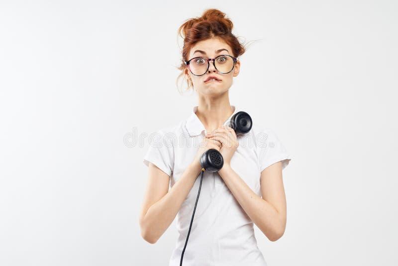 A mulher bonita nova em um fundo branco guarda um telefone da linha terrestre com vidros, olhos grandes, espaço para a cópia fotos de stock royalty free