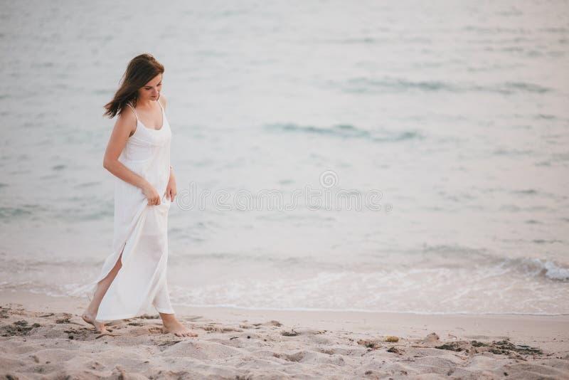 Mulher bonita nova em um vestido branco que anda em uma praia vazia perto do oceano fotos de stock
