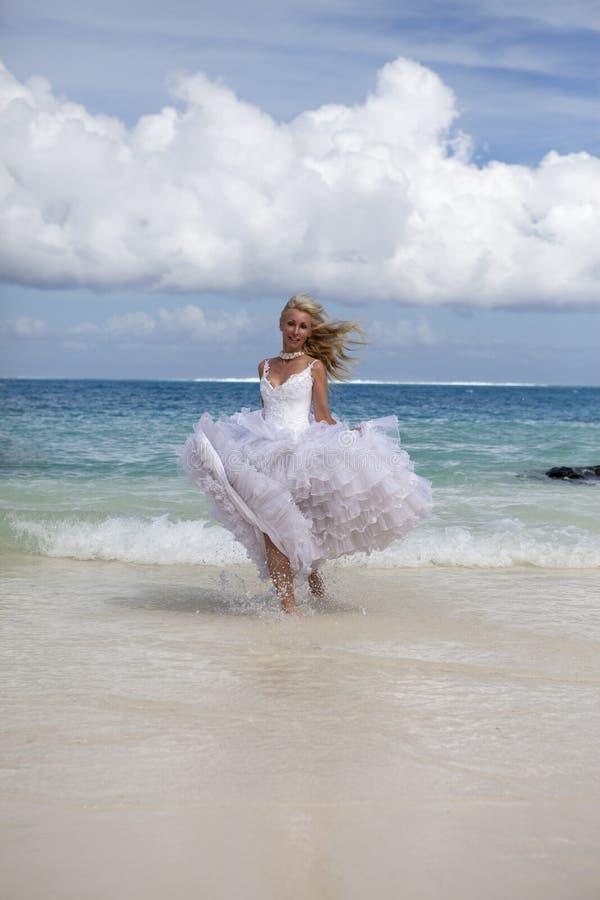 A mulher bonita nova em um vestido da noiva corre em ondas do mar imagens de stock royalty free