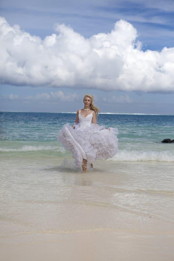 A mulher bonita nova em um vestido da noiva corre em ondas do mar fotografia de stock