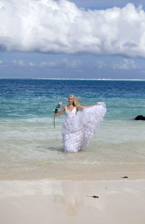 A mulher bonita nova em um vestido da noiva corre em ondas do mar foto de stock