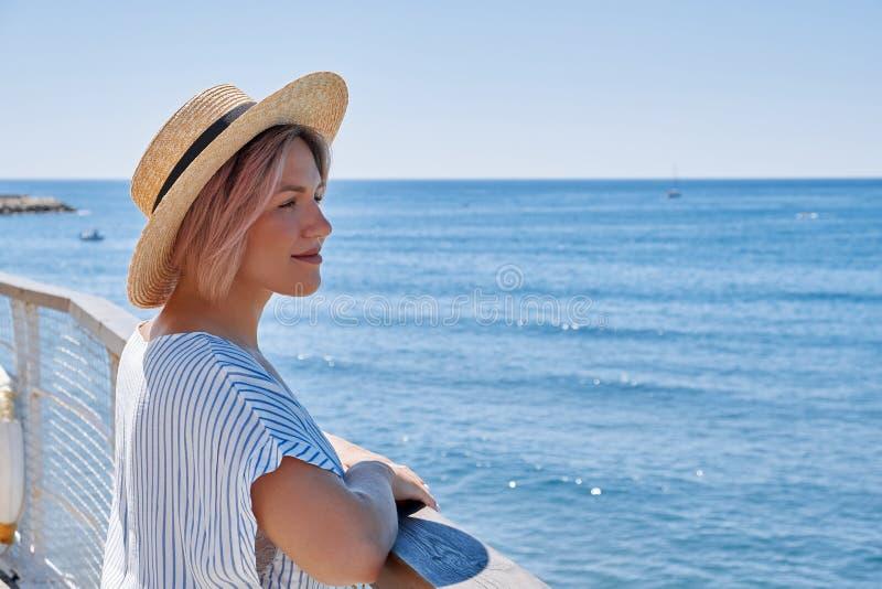 A mulher bonita nova em um vestido e em um chapéu está em um cais de madeira em um fundo de uma paisagem do mar foto de stock