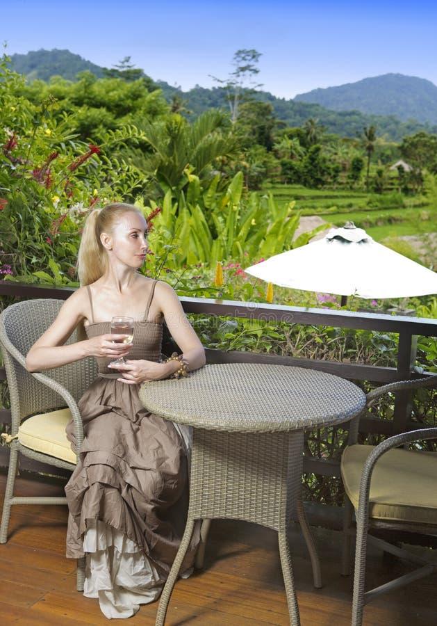 A mulher bonita nova em um vestido longo com um vidro do vinho olha a natureza tropical fotografia de stock royalty free