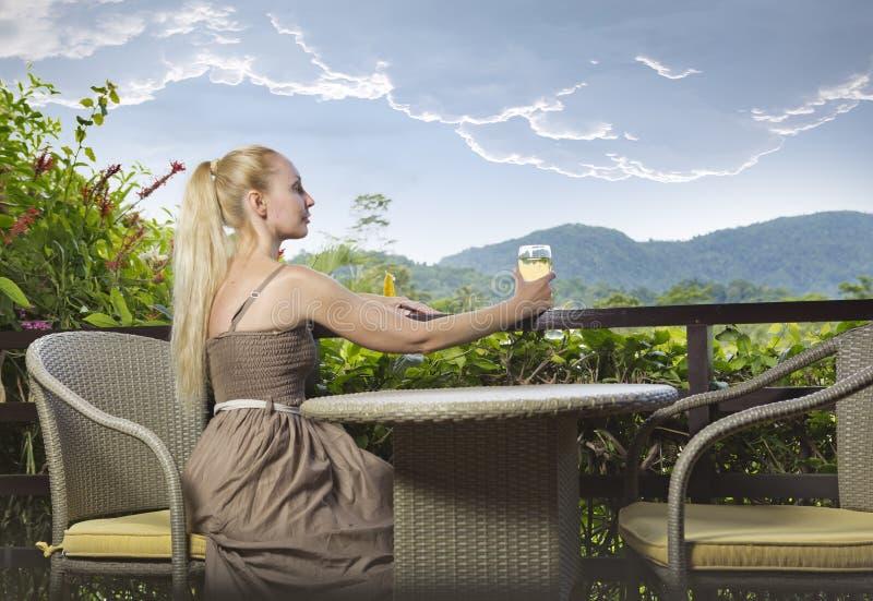 A mulher bonita nova em um vestido longo com um vidro do vinho olha a natureza tropical imagens de stock royalty free