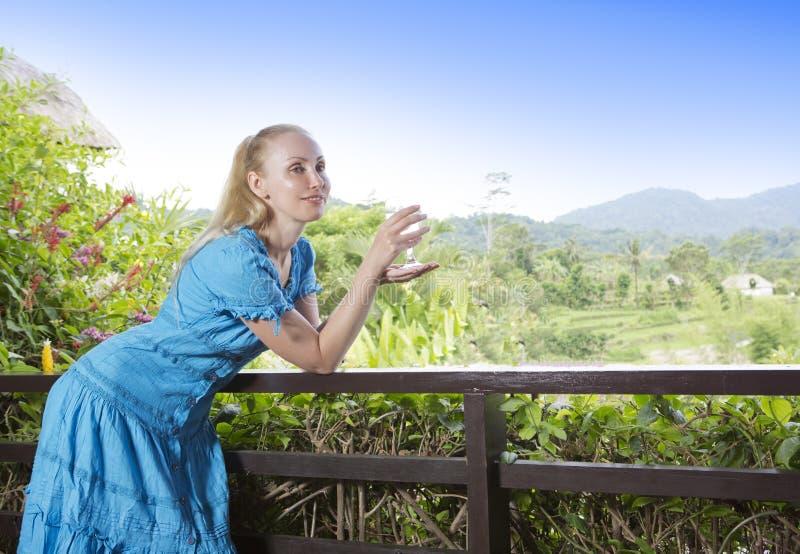 A mulher bonita nova em um vestido longo com um vidro do vinho olha a natureza tropical fotos de stock