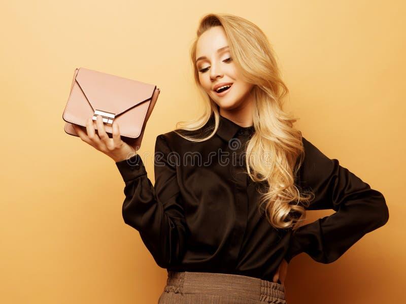 A mulher bonita nova em uma blusa marrom e em cal?as guarda uma bolsa e o levantamento em um fundo bege fotografia de stock