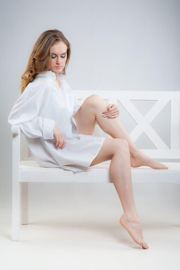 A mulher bonita nova em uma camisa de homens brancos est? sentando-se em um banco branco imagens de stock
