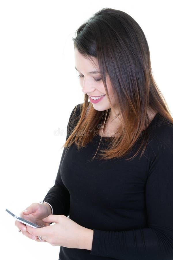 Mulher bonita nova entusiasmado que olha o sorriso do telefone celular Mensagem de texto da leitura da mulher isolada sobre o fun imagem de stock
