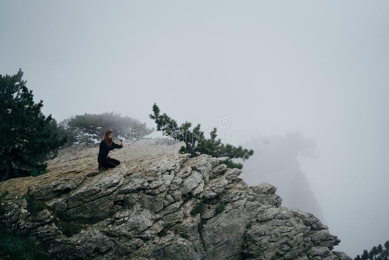 A mulher bonita nova está fazendo fotos na câmera na borda de um penhasco da montanha na névoa fotografia de stock royalty free