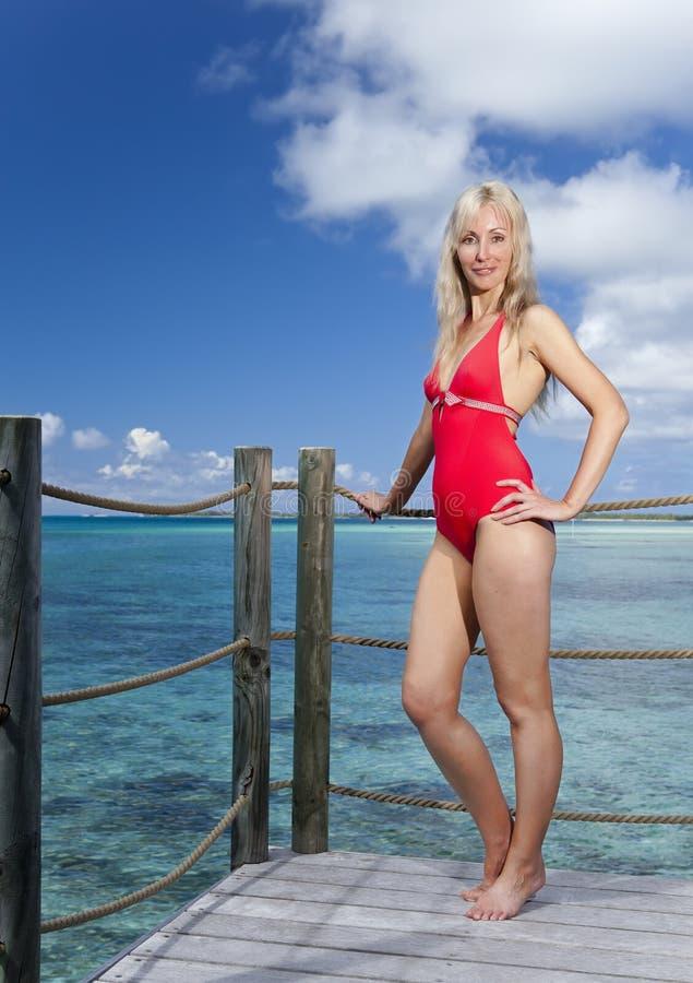 A mulher bonita nova está no maiô na plataforma na casa de campo na água foto de stock
