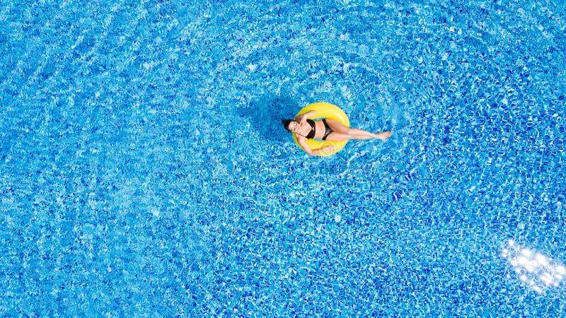 A mulher bonita nova está relaxando na piscina com anel amarelo de borracha foto de stock