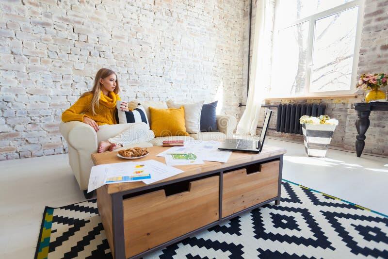 A mulher bonita nova está sentando-se em um sofá em um fundo branco da parede de tijolo com uma xícara de café Portátil, originai imagens de stock royalty free