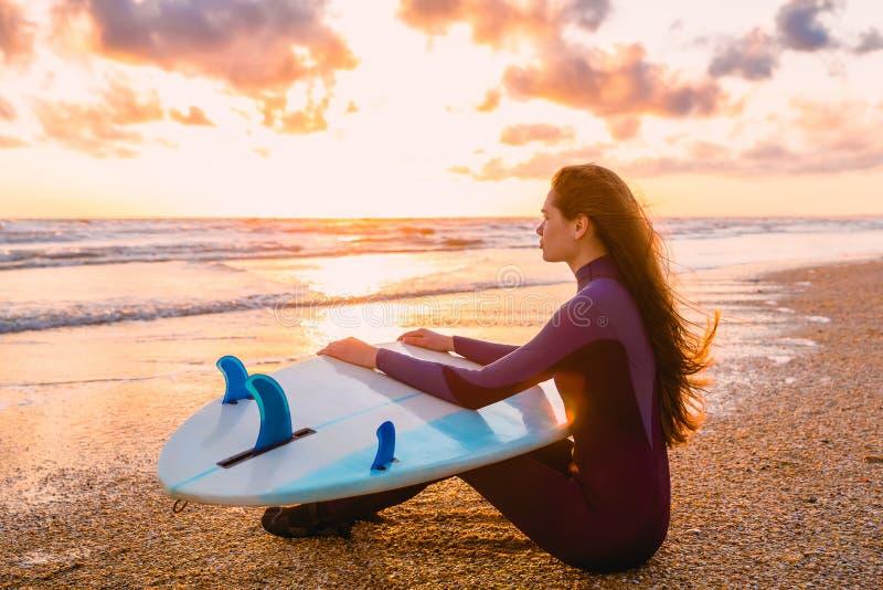 A mulher bonita nova está sentando-se na praia Surfe a menina com a prancha na praia no por do sol ou no nascer do sol Surfista e foto de stock