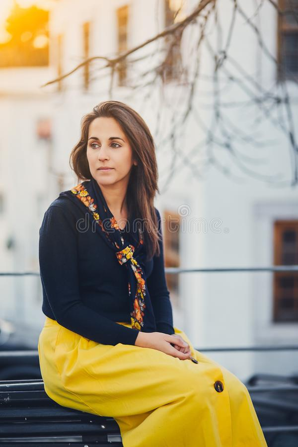 A mulher bonita nova está sentando-se na rua no banco no por do sol Retrato de uma menina sonhadora em uma saia amarela, sapatilh imagem de stock royalty free