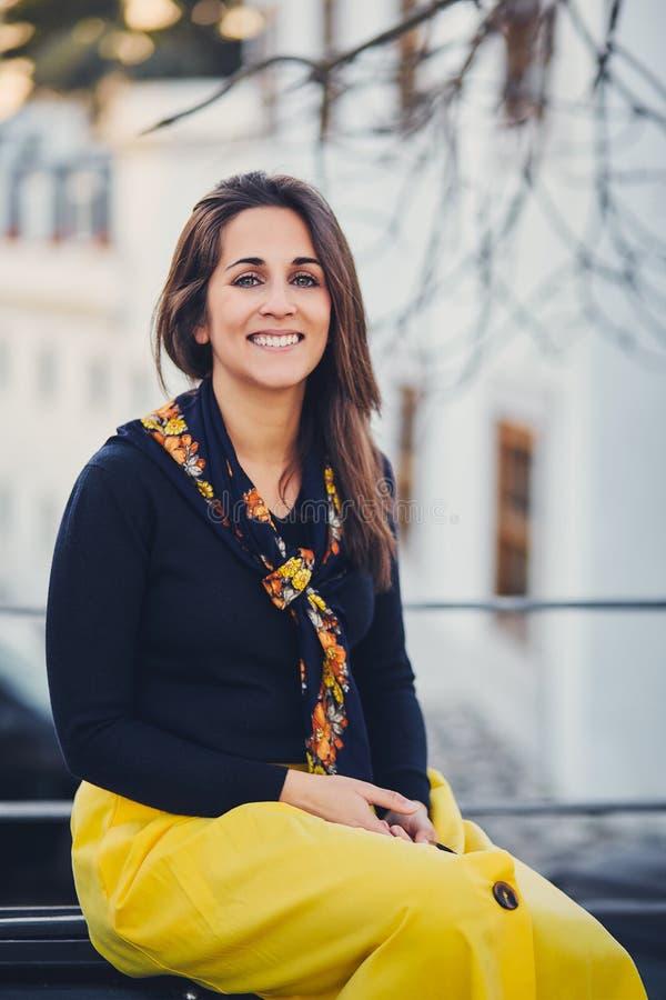 A mulher bonita nova está sentando-se na rua no banco no por do sol Retrato de uma menina de sorriso em uma saia amarela, sneake  imagens de stock