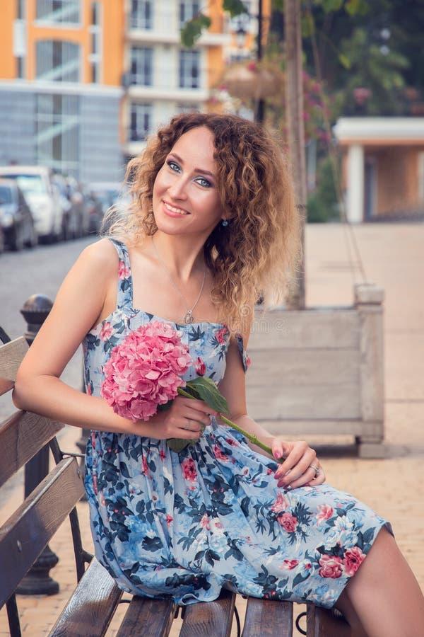 A mulher bonita nova está sentando-se no banco perto do centro de negócios Sorri felizmente, guarda uma flor da hortênsia em suas imagem de stock