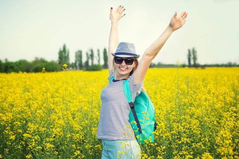 A mulher bonita nova est? andando ao longo de um campo de floresc?ncia em um dia ensolarado imagens de stock royalty free
