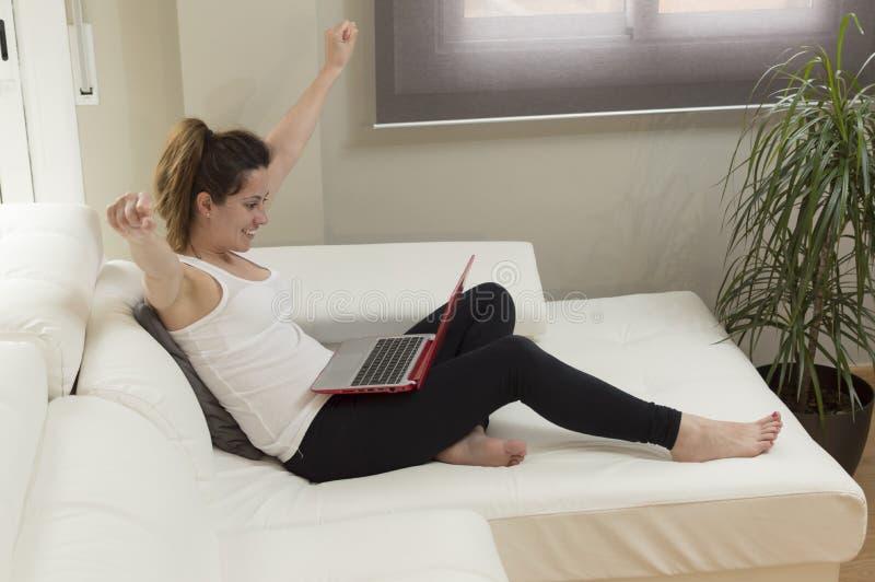 A mulher bonita nova feliz com o portátil no sofá arma-se acima fotografia de stock