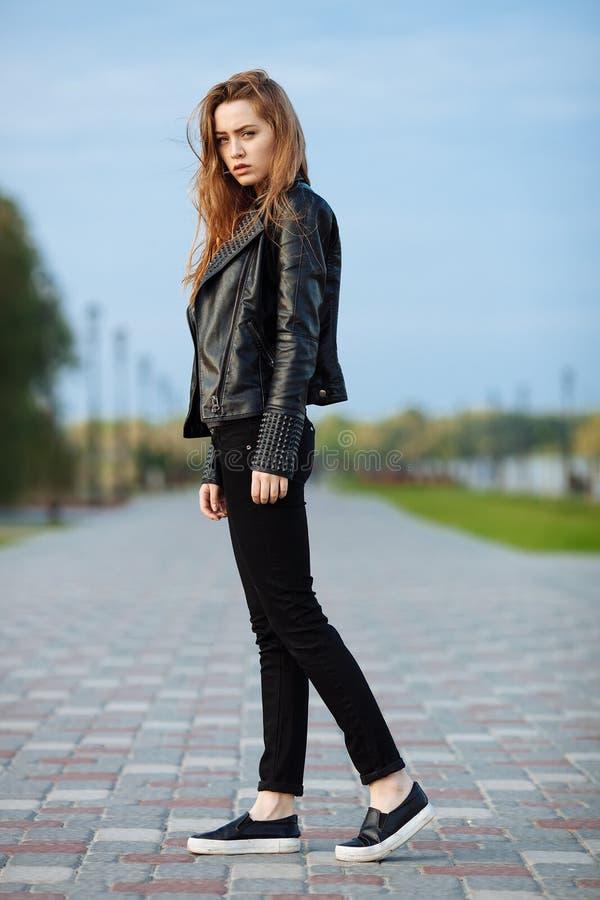 Mulher bonita nova feliz no mocassim preto das calças de brim do preto do casaco de cabedal que levanta para os testes modelo no  imagem de stock royalty free