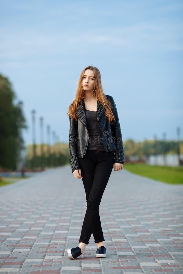 Mulher bonita nova feliz no mocassim preto das calças de brim do preto do casaco de cabedal que levanta para os testes modelo no  fotografia de stock royalty free