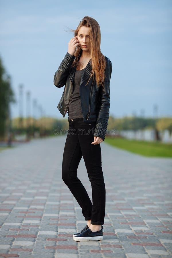 Mulher bonita nova feliz no mocassim preto das calças de brim do preto do casaco de cabedal que levanta para os testes modelo no  imagens de stock