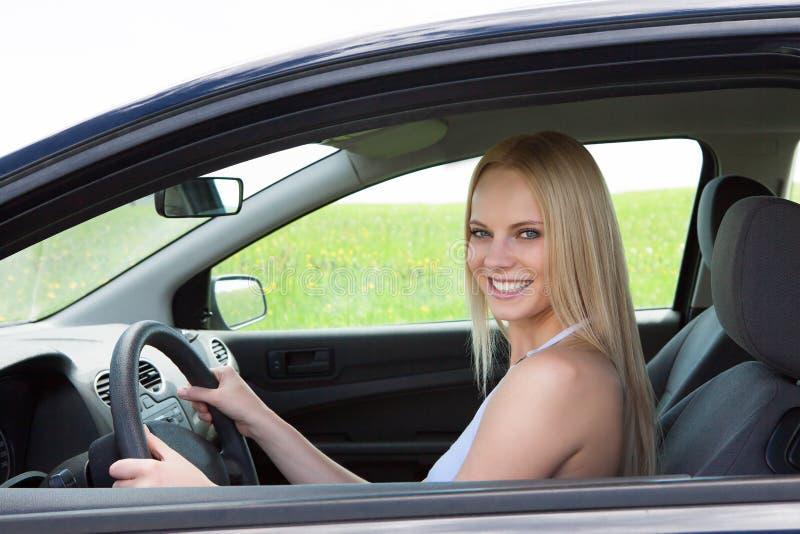 Mulher bonita nova feliz que conduz o carro imagens de stock royalty free