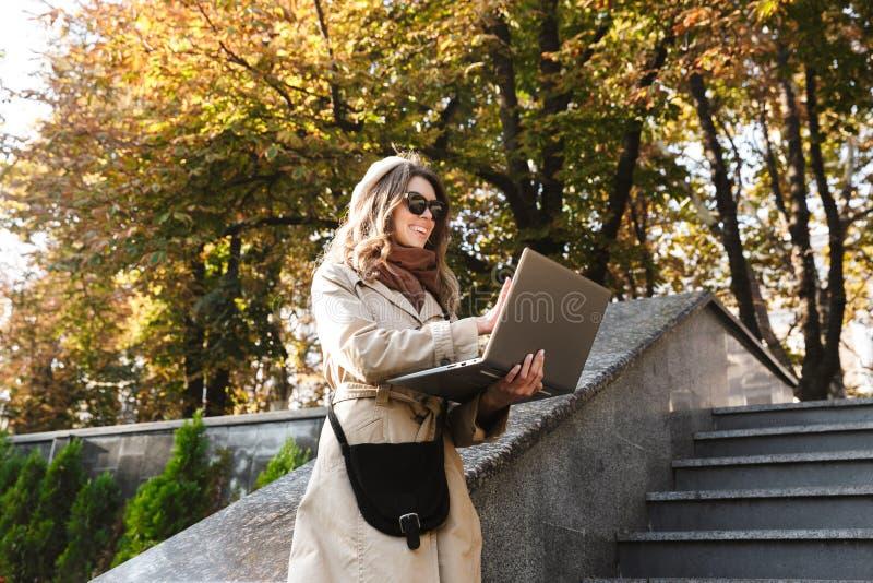 Mulher bonita nova fora no parque da rua usando o laptop foto de stock royalty free