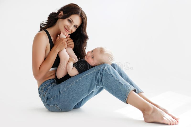 Mulher bonita nova, moreno com o cabelo longo, levantando no estúdio com seu filho pequeno fotografia de stock