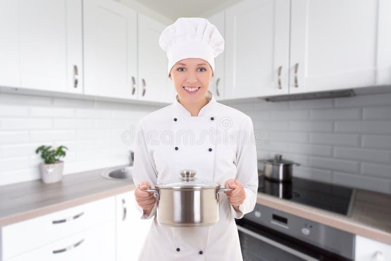 Mulher bonita nova na caçarola guardando uniforme do cozinheiro chefe em moderno fotografia de stock
