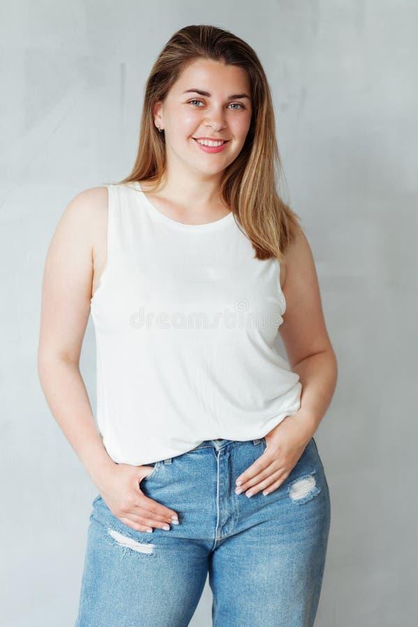Mulher bonita nova na camisa e nas calças de brim brancas fotografia de stock