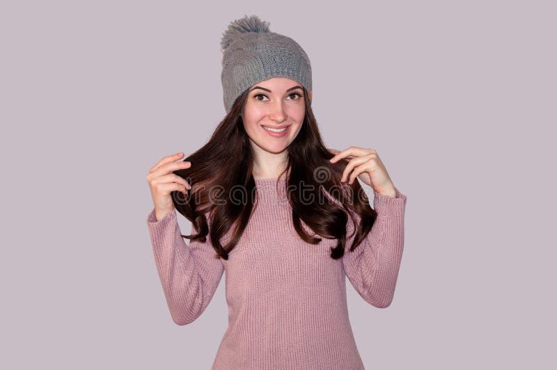 Mulher bonita nova na camiseta e no chapéu feito malha em Grey Background Conceito do inverno imagens de stock royalty free
